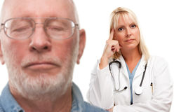 Concerned Senior Man and Female Doctor Behind. With Selective Focus the Doctor Royalty Free Stock Photo
