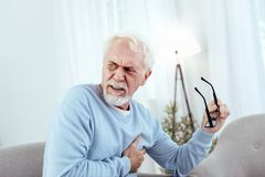 Concerned senior man having chest pain. Heart rhythm disturbances. Painful senior man touching chest and holding glasses Royalty Free Stock Photos