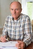 Concerned Senior Man Reviewing Domestic Finances. Senior Man Reviewing Domestic Finances Royalty Free Stock Image