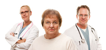 Concerned Senior Woman With Doctors Behind Stock Photos