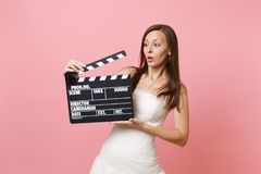 Concerned shocked bride woman in white wedding dress holding classic black film making clapperboard on pastel