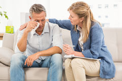 Concerned therapist comforting crying male patient Stock Images
