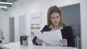 Thoughtful young lady in formal clothes attentively checking documents in the office standing at the counter. Woman with stock footage