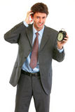 Concerned about time businessman with alarm clock Stock Photos