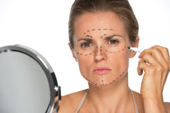 Concerned woman applying plastic surgery marks Royalty Free Stock Images
