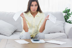 Concerned woman doing her accounts. Sat on a couch stock images
