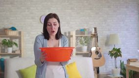 Concerned woman holding a bucket where water flows from the ceiling slow mo. Concerned woman holding a bucket where water flows from the ceiling in home slow mo stock footage