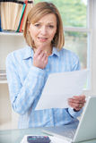 Concerned Woman In Home Office Looking At Letter Stock Photos