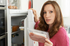 Concerned Woman Looking At Pre Packaged Meat Stock Image