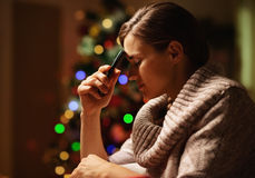 Concerned woman with mobile phone in front of christmas tree. Concerned young woman with mobile phone in front of christmas tree Royalty Free Stock Image