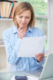 Concerned Woman Reading Letter In Home Office Royalty Free Stock Photo