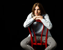 Concerned woman sitting on the red chair Royalty Free Stock Image