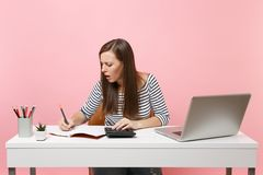 Concerned woman using calculator writing notes with calculations sit and work at office with contemporary pc laptop. Isolated on pastel pink background stock photography