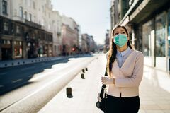 Concerned woman walking to work in public space during pandemic.Effect of the COVID-19.Protective measure,mask wearing.Respecting