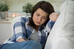 Concerned woman. Young concerned woman sitting on psychologist's couch Stock Photos