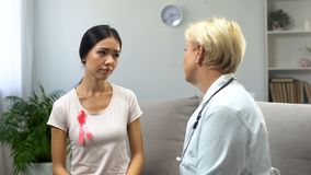Concerned woman consulting with mammologist, tumor in breast, cancer prevention stock photography