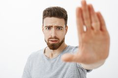 Concerned and worried handsome young male friend with blue eyes, beard and moustache pulling palm towards camera to warn. And stop from making bad choices Royalty Free Stock Images