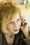 Concerned Young Blonde Woman on Mobile Phone Stock Photography
