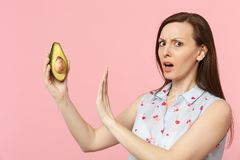 Concerned young girl in summer clothes showing stop gesture with palm to green avocado fruit isolated on pink pastel. Wall background. People vivid lifestyle royalty free stock photography
