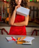 Concerned young housewife holding letter in christmas decorated. Kitchen Stock Images
