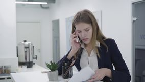 Concerned young lady in formal dress talking by cellphone checking papers in the office standing at the counter. Woman stock video footage