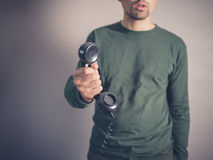 Concerned young man holding vintage phone Stock Images