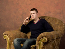 Concerned young man talking on his mobile Stock Photography