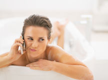 Concerned young woman in bathtub talking cell phone Stock Photos