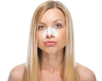Concerned young woman with clear-up strips on nose. Isolated on white Stock Photography
