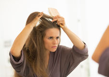 Concerned young woman combing hair in bathroom. Concerned young woman combing hair in modern bathroom Royalty Free Stock Image
