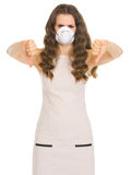 Concerned woman in cone mask showing thumbs down Royalty Free Stock Images