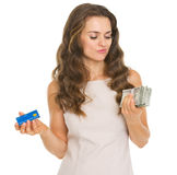 Concerned young woman with credit card and dollars Stock Images