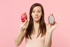 Concerned young woman holding in hand halfs of fresh ripe pitahaya, dragon fruit isolated on pink pastel wall background. In studio. People vivid lifestyle royalty free stock photo