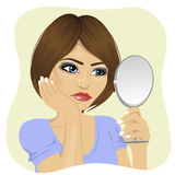 Concerned young woman looking at herself in mirror Royalty Free Stock Image