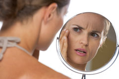 Concerned young woman looking in mirror Royalty Free Stock Images
