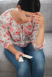 Concerned young woman looking on pack of pills Royalty Free Stock Photography