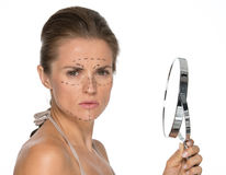 Concerned young woman with plastic surgery marks. And mirror Stock Photography