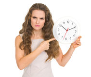 Concerned young woman pointing on clock Royalty Free Stock Photos