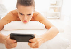Concerned young woman reading sms while laying on massage table Royalty Free Stock Image