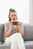 Concerned young woman sitting on sofa and reading sms Stock Photos