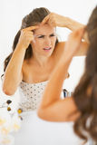 Concerned young woman squeezing acne. In bathroom Stock Photo