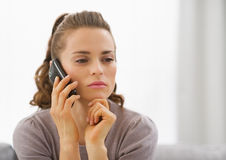 Concerned young woman talking cell phone. In living room Royalty Free Stock Images