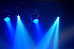 Concert. Blue light with spotlights illuminating the stage Royalty Free Stock Photos