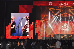 Concert of Atostrad performin on stage of Dubai Design Districy. Autostrad  singers with sunglasses performing on Red color stage, guitarist on big screen Stock Photos