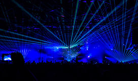 Concert. Bright laser show in the crowd of merry men Stock Photos