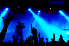Concert Crowd. Cheering crowd at concert, bright red lights from stage Royalty Free Stock Photography
