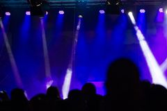 Concert crowd attending a concert, people silhouettes are visibl. E, backlit by stage lights. Raised hands and smart phones are visible here and there Royalty Free Stock Photography