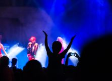 Concert crowd attending a concert, people silhouettes are visible, backlit by stage lights. Raised hands and smart phones are visi. Ble here and there royalty free stock photo