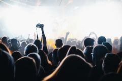 Concert crowd in bright light. Concert crowd in bright blue light. Person lifts a hand with a camera Royalty Free Stock Images
