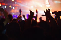 Concert crowd. In front of stage-lights raising hands Stock Images